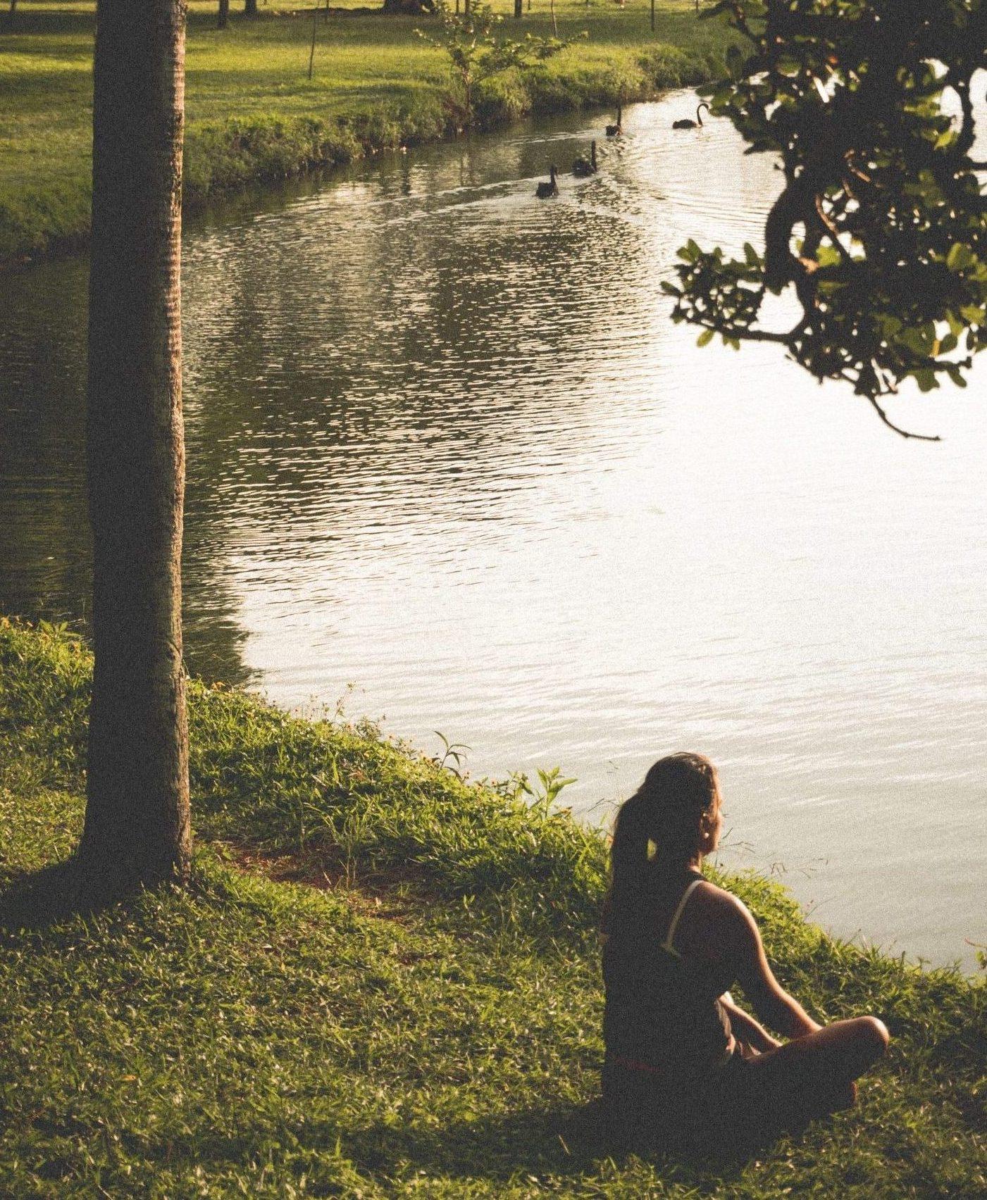 woman-sitting-on-grass-by-lake-290627
